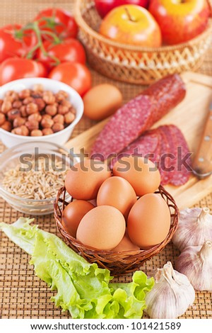 Ingredients for breakfast: tomatoes, eggs, sausage, garlic, peanuts, apples and lettuce.