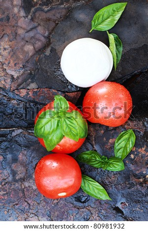 Ingredients for Caprese Salad. Mozzarella cheese, fresh basil, and tomatoes on a rustic slate background. - stock photo