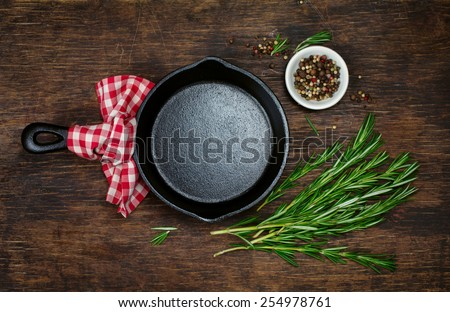 Ingredients for cooking and empty cast iron skillet, pepper and rosemary - stock photo