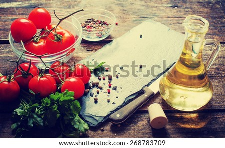 Ingredients for cooking and empty cutting board on an old wooden table. Food background with copyspace - stock photo