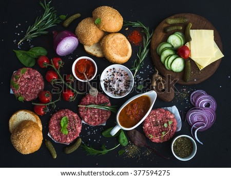 Ingredients for cooking burgers. Raw ground beef meat cutlets, buns, red onion, cherry tomatoes, greens, pickles, tomato sauce, cheese, herbs and spices over black background, top view, horizontal - stock photo