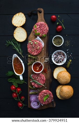 Ingredients for cooking burgers. Raw ground beef meat cutlets on wooden board, buns, red onion, cherry tomatoes, greens, pickles, tomato sauce, cheese, herbs and spices over black background, top view - stock photo