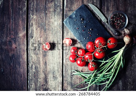 Ingredients for cooking  fresh tomato salad( raw tomatoes , green onion) over dark wooden table  - stock photo