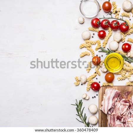 Ingredients for cooking fusilli pasta with bacon vegetables, spices and herbs  border, place for text on wooden rustic background top view - stock photo