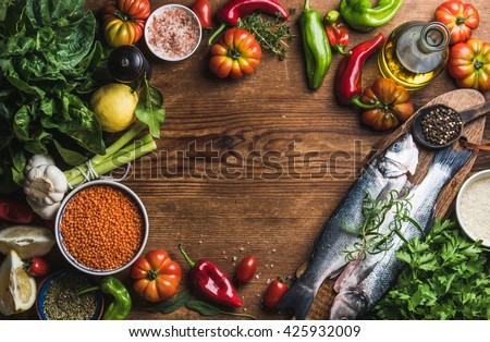 Ingredients for cooking healthy dinner. Raw uncooked seabass fish with vegetables, grains, herbs and spices over rustic wooden background. Copy space, top view - stock photo