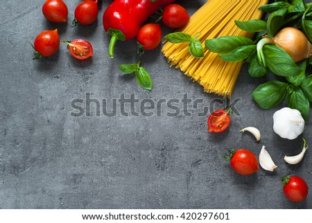 Ingredients for cooking Italian pasta - spaghetti, tomatoes, basil and garlic. Top view with space for taxt. - stock photo