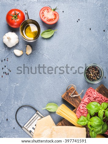 Ingredients for cooking pasta Bolognese. Spaghetti, Parmesan cheese,  tomatoes, grater, olive oil, garlic, minced meat, pepper and  basil on grey concrete background, top view, copy space, vertical - stock photo