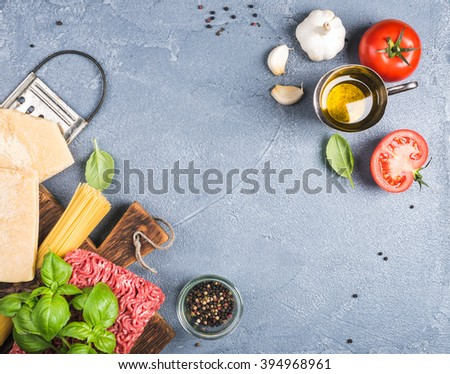 Ingredients for cooking pasta Bolognese. Spaghetti, Parmesan cheese,  tomatoes, metal grater, olive oil, garlic, minsed meat, pepper and fresh basil on grey concrete background, top view, copy space - stock photo