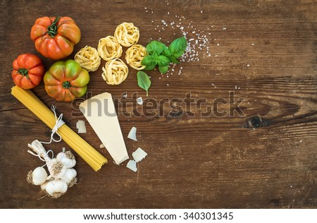 Ingredients for cooking pasta. Spaghetti, olive oil, garlic, Parmesan cheese, tomatoes and fresh basil on black slate background, top view, copy space - stock photo