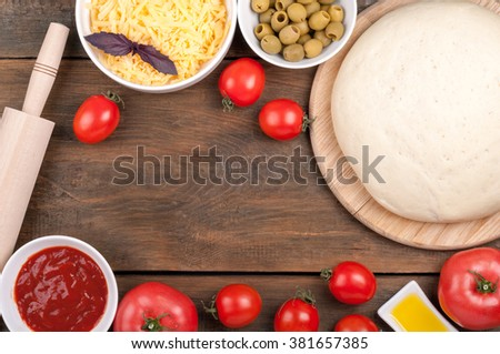 Ingredients for cooking pizza. Dough, rolling pin, tomatoes, olive oil, olives, tomato sauce, basil and cheese on a wooden table - stock photo