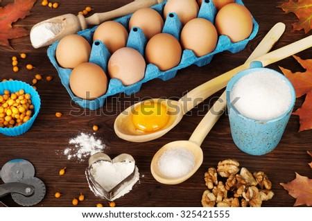 Ingredients for cooking; recipes; eggs; yolk; wooden spoons; Blue cup; sugar; Sugar in a wooden spoon; background for recipes; autumn menu; autumn background - stock photo