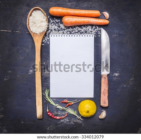 ingredients for cooking rice with vegetables, a knife, a wooden spoon, lemon, spicy, pepper, garlic lined frame with  sheet of paper text area on wooden rustic background top view close up - stock photo