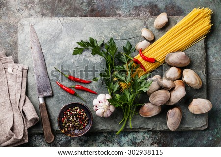 Ingredients for cooking Spaghetti vongole Shells vongole and raw sapaghetti on stone slate background - stock photo