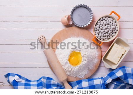 Ingredients for dough flour on wooden board, egg, butter and tartlet tins, ceramic  baking beans  on white wooden background. Selective focus.  - stock photo