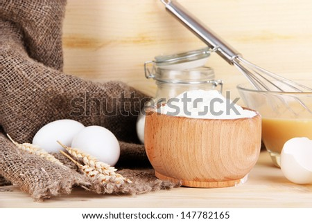 Ingredients for dough on wooden table on wooden background