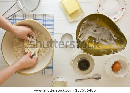 Ingredients for English scones laid out on white wood, with butter being rubbed into flour. Part of a series showing the preparation of scones. - stock photo
