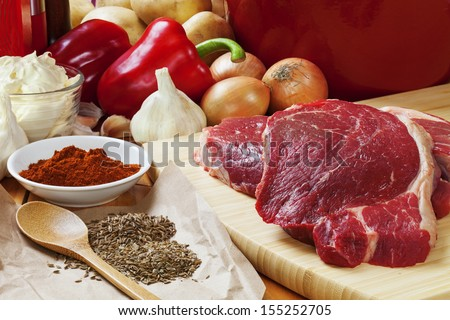 Ingredients for goulash. Raw beef skirt steak, onions, red capsicums, garlic, sour cream, paprika, caraway seeds and dill seeds, and potatoes to serve. - stock photo