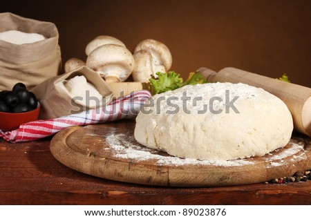ingredients for homemade pizza on wooden table on brown background - stock photo