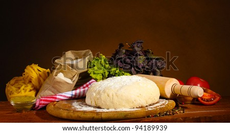 ingredients for homemade pizza on wooden table on brown background