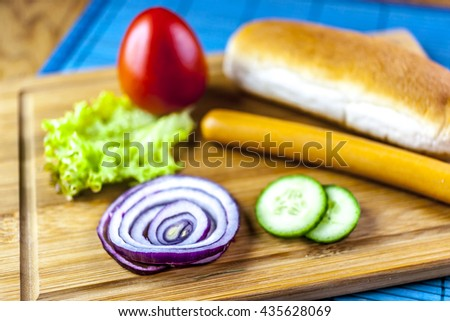 ingredients for hot-dog on wooden board