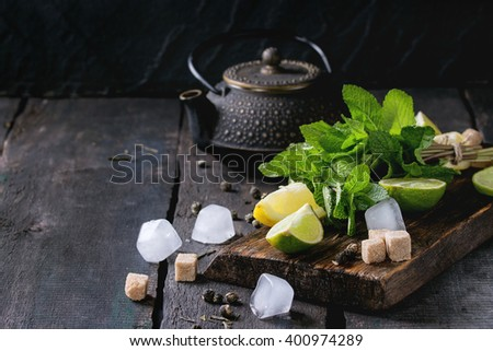 Ingredients for ice green tea lime, lemon, mint, sugar, green tea and ice cubes on wooden chopping board with black iron teapot over old wooden background. Rustic style.