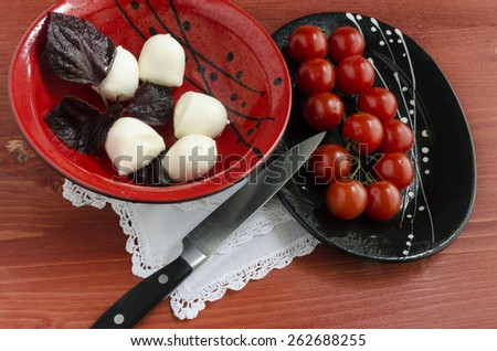 Ingredients for Italian caprese salad with fresh basil leaves, tomato and  mozzarella  on red wooden table. Overhead view. From series Natural organic food - stock photo