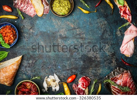 Ingredients for italian snack, bruschetta, crostini or sandwich bar with italian ham, sausage  and antipasto on rustic wooden background, top view, frame - stock photo