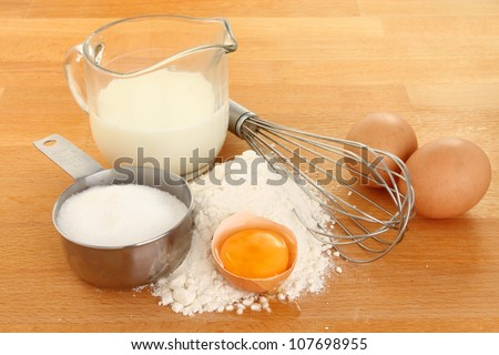 Ingredients for making batter, eggs,flour, milk and sugar with a whisk on a wooden worktop, - stock photo