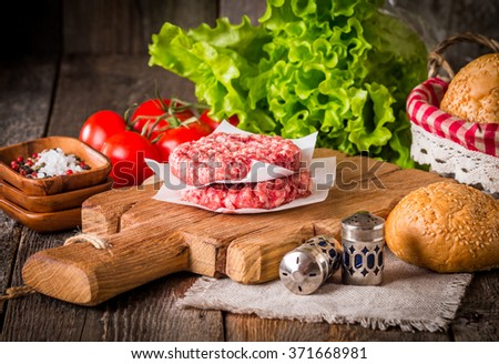 Ingredients for making homemade burger on wooden cutting board - stock photo