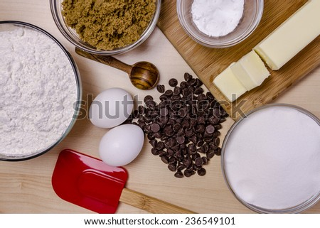 Ingredients for making homemade chocolate chip cookies with red spatula