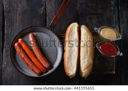 Ingredients for making homemade hot dogs. Sausages in pan, fresh baked buns, mustard and ketchup sauce, served on wood chopping board over old wooden background. Rustic style. Flat lay