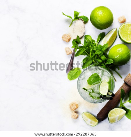 Ingredients for making mojitos (ice cubes, mint leaves, sugar and lime on rustic background) - stock photo