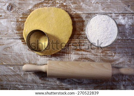 Ingredients for making pastry with flour rolled dough and mould for baking on wooden table top in flour, horizontal picture - stock photo