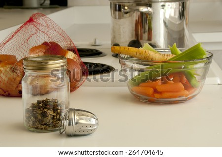 Ingredients for making soup, spices, onions, parsnips, celery, pot all placed on the kitchen counter top - stock photo