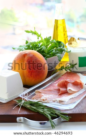 Ingredients for meal preparation yogurt,  goat cheese, olive oil, ham, rosemary,peach,arugula
