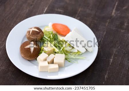 Ingredients for Mizutaki, a Japanese hot pot dish, including Chinese cabbage, mizuna (Japanese mustard), shiitake mushrooms, carrot, and two kinds of tofu  - stock photo