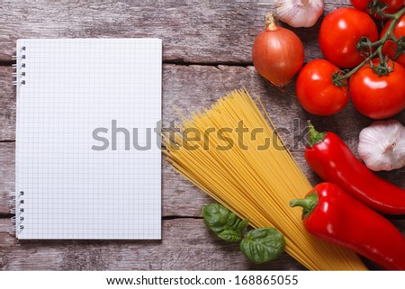 Ingredients for pasta: spaghetti, vegetables and spices and a notepad on the old table. top view - stock photo