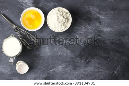Ingredients for pastries: flour, eggs, milk against a dark background - stock photo