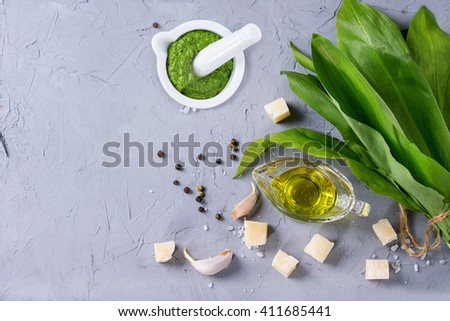 Ingredients for pesto and ramson pesto in ceramic mortar. Bunch of ramson, olive oil, parmesan cheese, garlic, salt and pepper over gray textured background. Flat lay with copy space - stock photo
