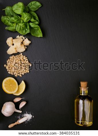 Ingredients for pesto sauce preparing on black slate background - stock photo