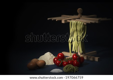 Ingredients for preparing a traditional Italian pasta with taglitelli hanging on a wooden frame, cherry tomatoes, flour, eggs and parmesan cheese on a kitchen counter, dark background with copyspace - stock photo