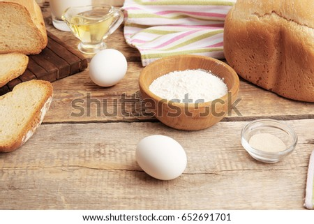 Ingredients for preparing bread in machine on wooden table