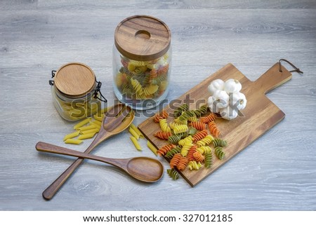 Ingredients for preparing macaroni  on a wood table with wood plate - stock photo