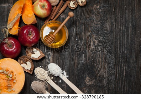 Ingredients for pumpkin and apple pie. Apples, nuts, pumpkin, honey, flour, eggs, oatmeal, sugar on vintage wooden background.  - stock photo