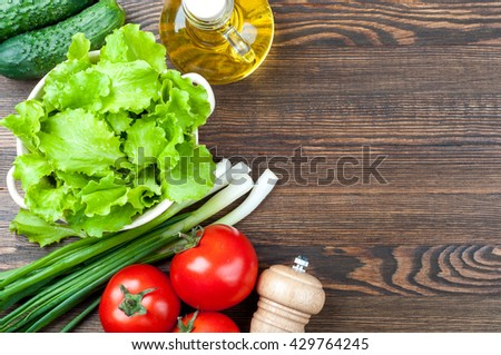 Ingredients for salad. Healthy food concept background with copy space. Organic vegetables - lettuce, green onions, tomatoes and olive oil, salt on wooden table. Top view - stock photo