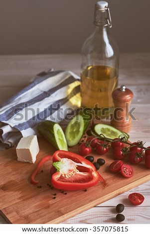 Ingredients for salad. Peppers, cherry tomatoes, olives, cucumbers, cheese and butter on the wooden table. Rustic Style.