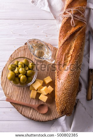Ingredients for sandwich with cheese, baguette and olives on wooden background