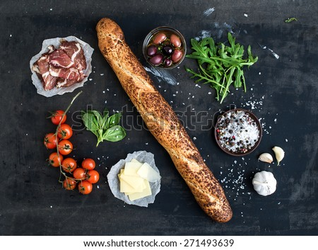 Ingredients for sandwich with smoked meat, baguette, basil, arugula, olives, cherry-tomatoes, parmesan cheese, garlic and spices over black grunge background. Top view. - stock photo