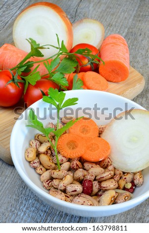 ingredients for soups legumes in water with carrot onion and tomato