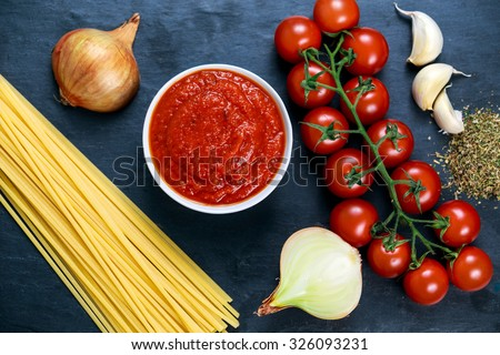 Ingredients for Spaghetti with marinara sauce.  Ready to Cook. On blue background. - stock photo